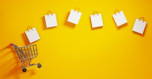 Shopping bags and a shopping cart on yellow background. Horizontal composition with  copy space. Shopping concept.